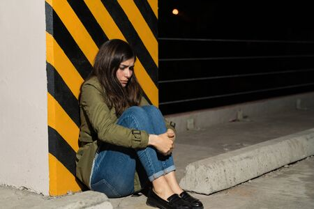 Full length of sad woman hugging knees while sitting against striped column in parking lot at night