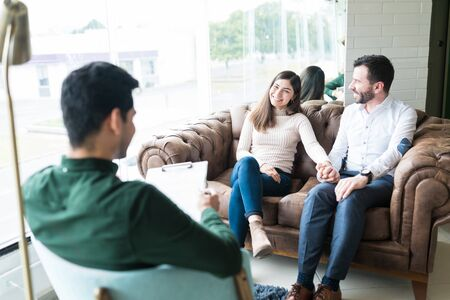 Reconciled happy couple holding hands while talking to young therapist in office