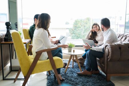 Professionals with laptop sharing ideas in meeting at office