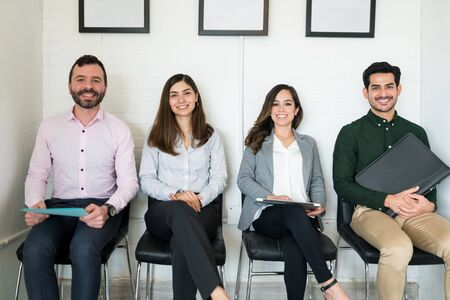 Smiling confident applicants waiting for job interview at office