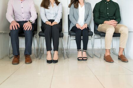 Low section of male and female candidates in formalwear sitting at office while waiting for interview Фото со стока