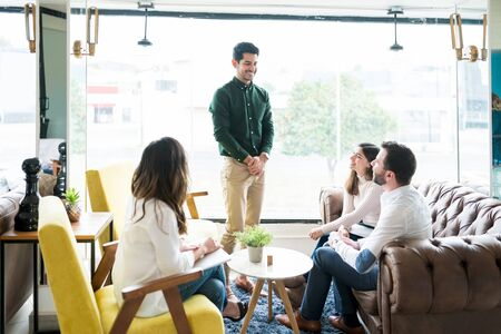 Employee discussing with coworkers in meeting at working space