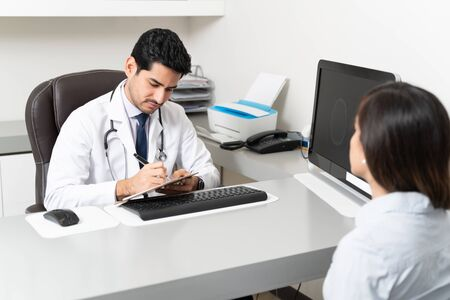 Latin male doctor writing medical prescription while sitting at desk in clinic Reklamní fotografie