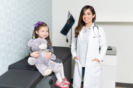 Confident Caucasian female pediatrician with cute little girl in her office Reklamní fotografie