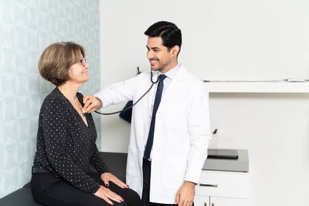 Confident male doctor checking smiling senior woman with stethoscope on examination table in hospital Reklamní fotografie - 141061085