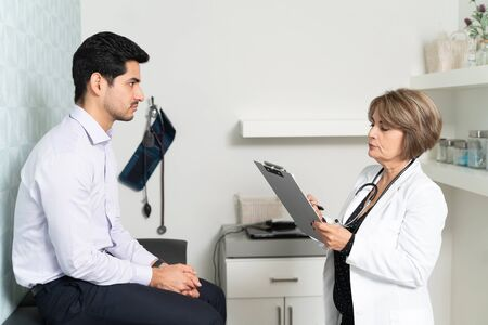 Senior female doctor examining medical record while male patient sitting in clinic