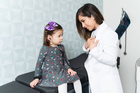 Cute girl listening heartbeats female pediatrician with stethoscope during checkup
