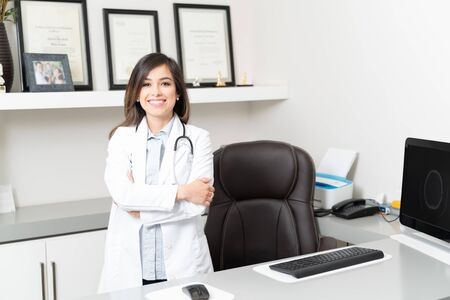 Confident Caucasian female doctor standing with arms crossed at desk in office
