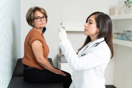 Confident female geriatrician preparing syringe to inject senior woman sitting on examination table