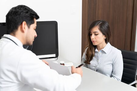 Latin male doctor discussing with patient over medical prescription at clinic