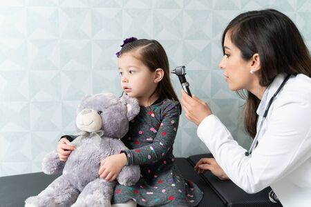 Caucasian female pediatrician examining girls ear with otoscope in clinic Reklamní fotografie
