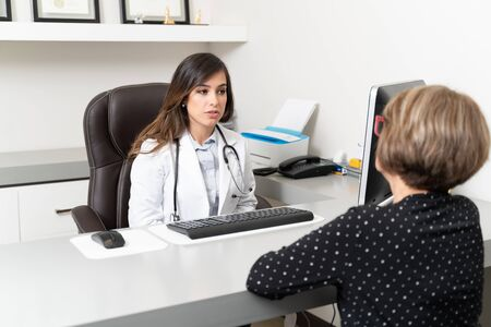 Confident female doctor discussing with senior woman at desk in clinic