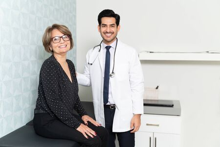 Confident Hispanic male physician with senior patient in hospital Reklamní fotografie