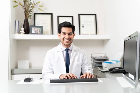 Confident male doctor using computer while sitting at desk in office
