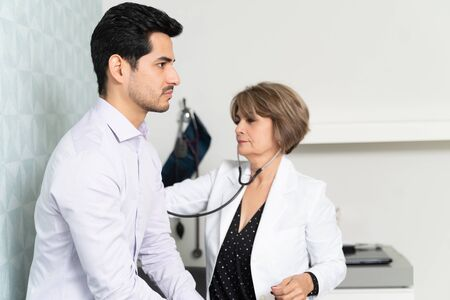 Female family doctor examining male patient with stethoscope in clinic