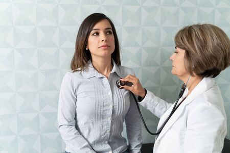 Senior physician checking female patient with stethoscope in clinic Reklamní fotografie