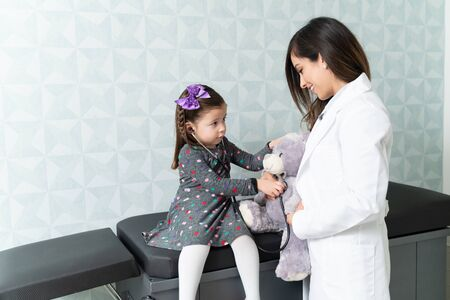 Cute girl checking teddy bear with stethoscope being held by female pediatrician in clinic