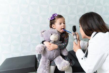 Caucasian female pediatrician examining girls mouth with otoscope Reklamní fotografie