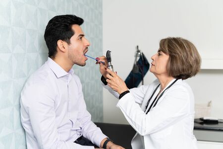 Female family doctor checking Hispanic man in clinic