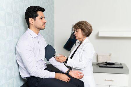 Elderly female doctor checking man with sphygmomanometer in hospital
