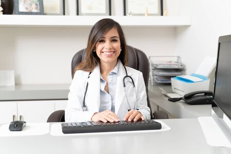 Confident female doctor using computer while sitting at desk in office