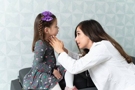 Confident female doctor examining thyroid gland of girl during medical exam