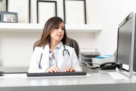 Female doctor using computer while sitting at desk in clinic