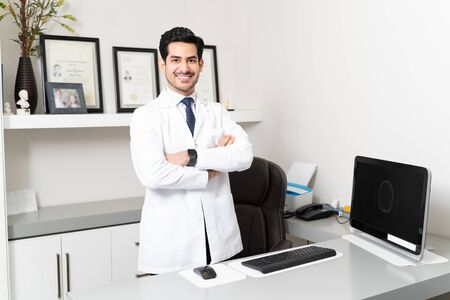 Confident Latin male doctor standing with arms crossed at desk in clinic