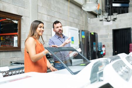 Confident supervisor explaining young woman while looking away by washing machine in appliance store