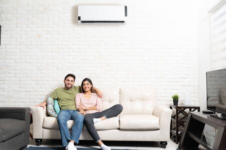 Portrait of smiling Hispanic couple relaxing on sofa in living room at home with air conditioning