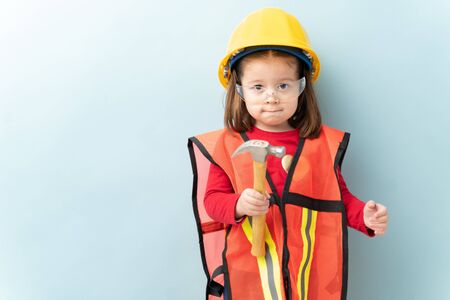 Beautiful little girl aspiring to work in construction and wearing a helmet and a vest and using a hammer 免版税图像