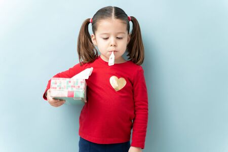 Portrait of a cute little girl with ponytails checking her temperature with a termometer