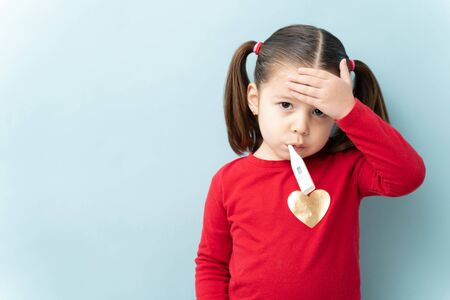 Pretty little girl with ponytails touching her forehead and using a thermometer to check for a fever in a studio 스톡 콘텐츠