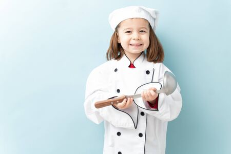 Pretty little three year old dressed up as a chef and getting ready to cook with a spoon in a studio Stock Photo