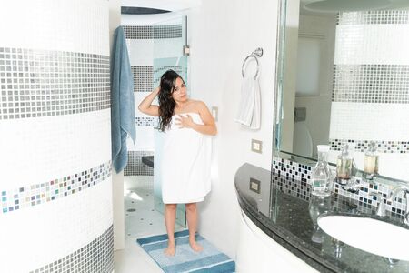 Full length view of a young woman wrapped up in a towel and getting out of the shower Archivio Fotografico