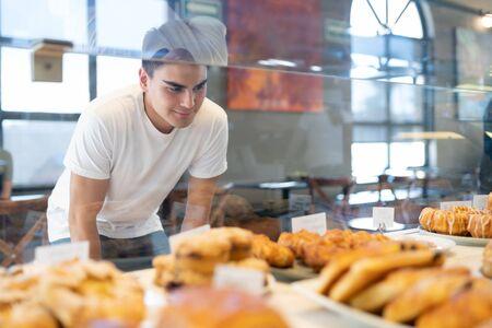 Attractive Hispanic man looking through a glass and choosing some bread and pastries in a bakery shop