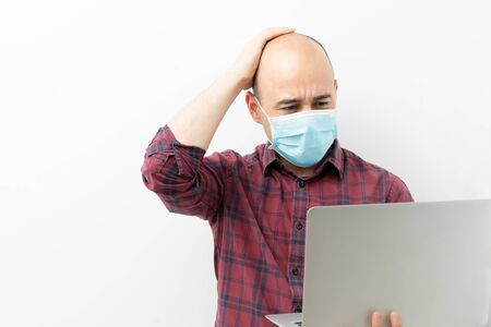Young man with surgical mask looking worried and stressed while looking at his laptop computer