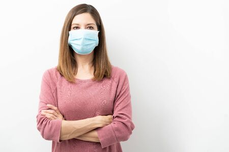 Woman in her 40s wearing a surgical mask with arms crossed during coronavirus covid19 pandemic