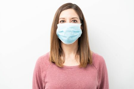 Portrait of a woman in her 40s wearing a surgical mask and looking serious in a studio