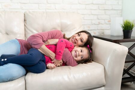 Portrait of a beautiful family of mom and daughter embracing and cuddling in a couch at home