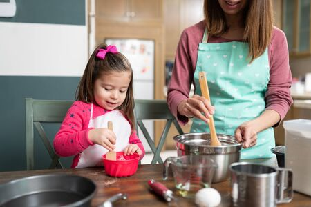 Pretty little girl wearing and apron and getting ready to bake some cookies with her mom in the kitchen