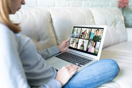 Closeup of a woman looking at her laptop at home while doing a video call with some of her friends and family