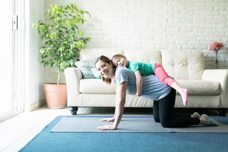 Portrait of a beautiful little girl hoping onto her mother's back while she exercises on a yoga mat at home