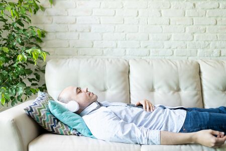 Profile view of a Caucasian man lying on a sofa at home and listening to a guided meditation and practicing mindfulness with headphones on