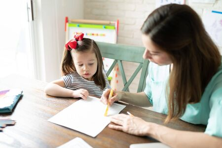 Mother explaining an activity and giving instructions to her little daughter while teaching and homeschooling