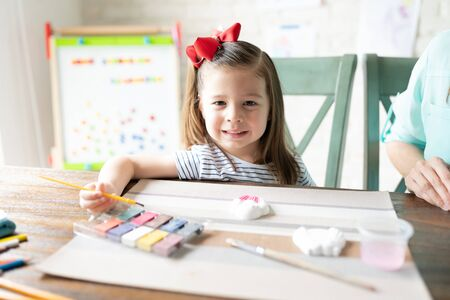 Cute little three year old using watercolors to paint a plaster cupcake figure and enjoying homeschool with her mom Reklamní fotografie
