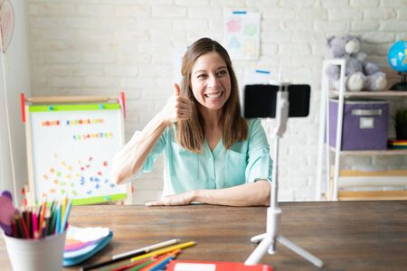 Caucasian female teacher giving thumbs up and saying good job to her students while on a video call on her smartphone