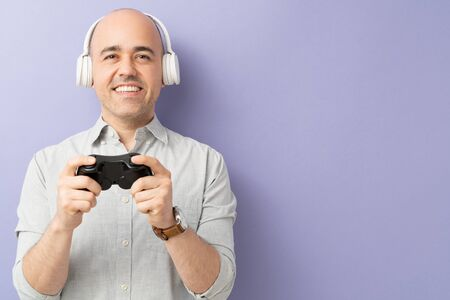 Nerdy bald man wearing headphones and playing video games with a controller in a studio with a lot of copy space