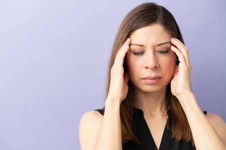 Closeup of a Caucasian woman feeling stressed and closing her eyes while having a headache Stok Fotoğraf