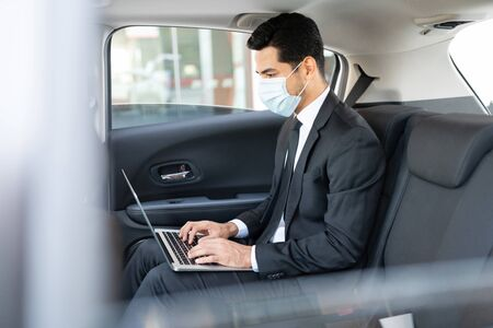 Young businessman wearing face mask while using laptop in taxi during coronavirus outbreak